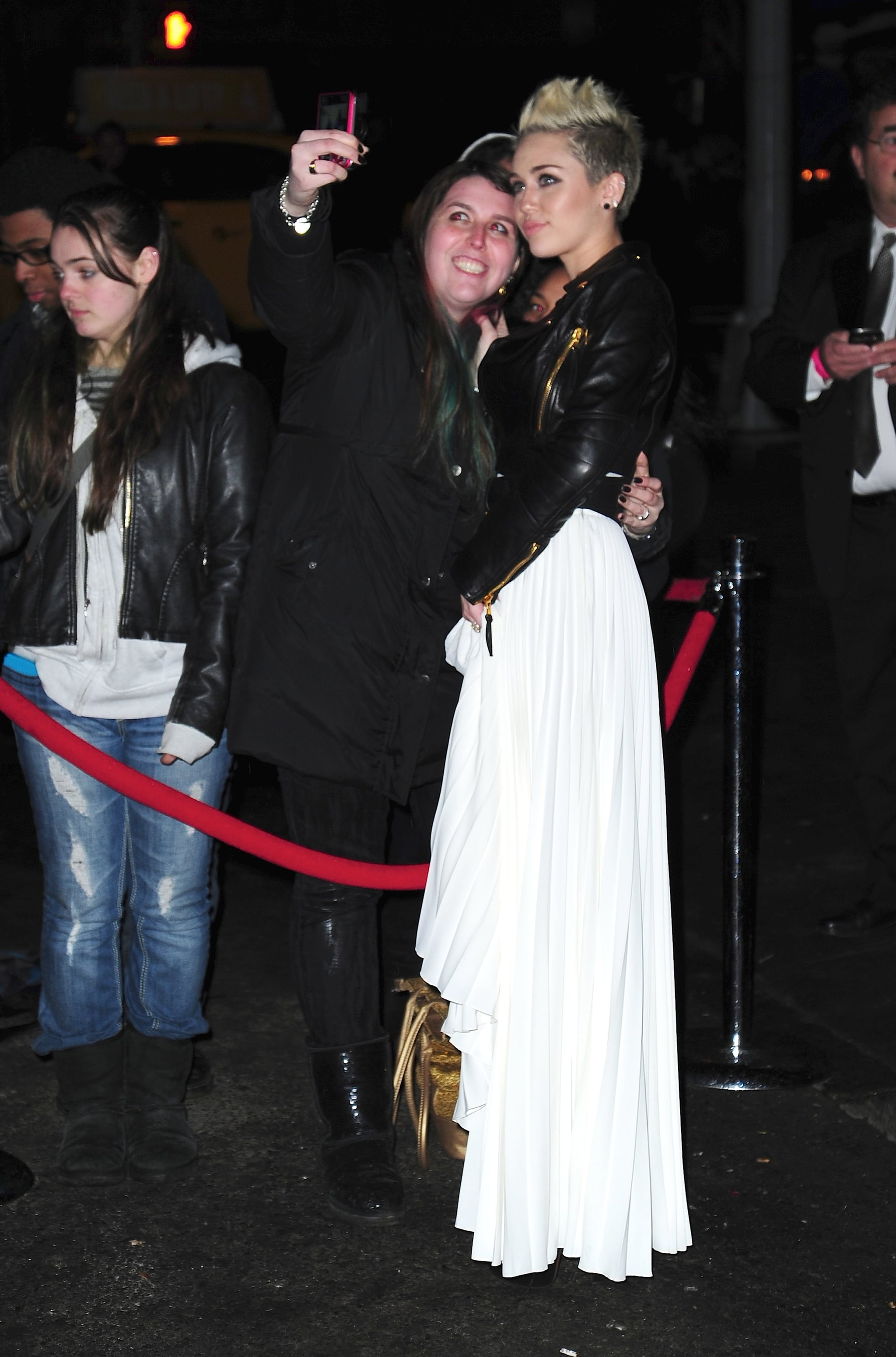 Miley Cyrus posed for pictures with fans on her way into the party.