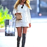 Candice Swanepoel wearing a Chanel bag and Stuart Weitzman boots.