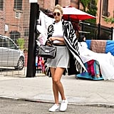 Gigi wore a white crop top, sporty Lucy Paris skater skirt ($65), and her signature shoes — easy walking sneakers —when she stepped out between shows. She balanced a black and white statement coat on her shoulders and completed her ensemble with round sunglasses and a black satchel.