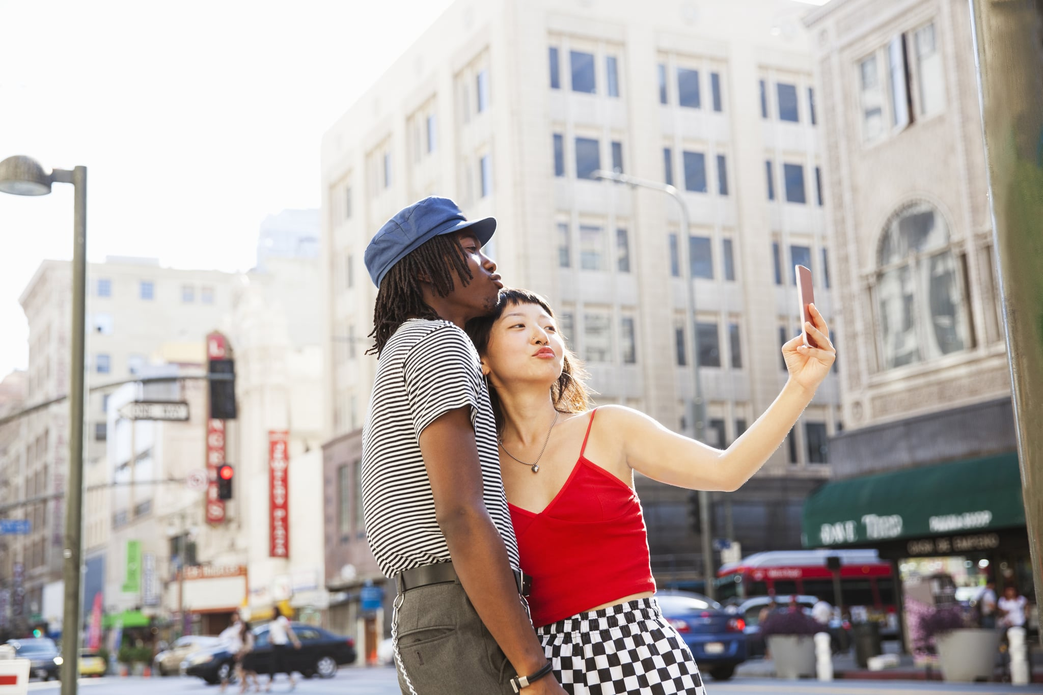 A young couple taking a selfie on a city street with a mobile device