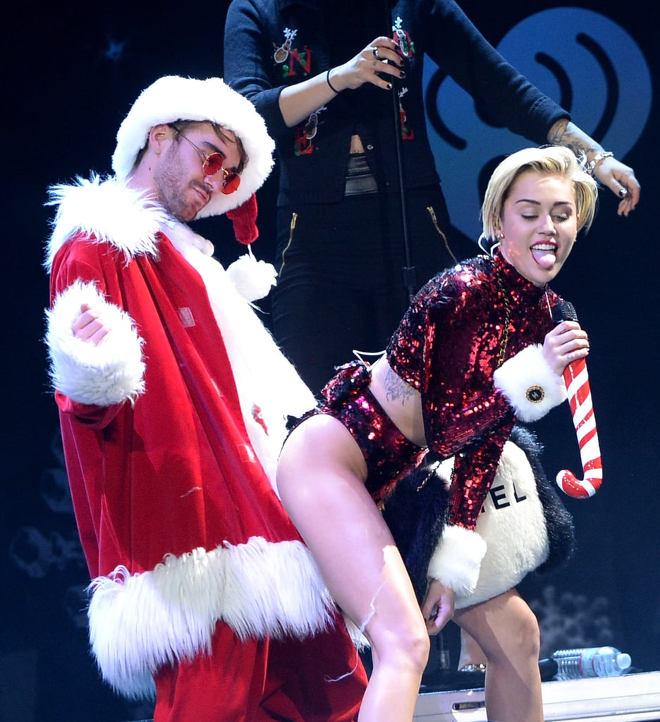 "Miley Cyrus may have made Mrs. Claus jealous when she got up close and personal with Santa at KIIS-FM's Jingle Ball in LA yesterday. The singer donned a shiny, red crop top with white cuffs for her theatrical performance, and she showcased her signature stage antics, twerking and sticking out her tongue while singing into a candy-cane microphone. The extended performance marks a return to flirty form for Miley, who gave us a purr-heavy rendition of ""Wrecking Ball"" with a lip-synching cat at the American Music Awards last month. Fans at the star-studded concert were also treated to festive performances by Selena Gomez, who rocked the stage with a short bob haircut, plus Robin Thicke, Enrique Iglesias, Ariana Grande, and more. This is just the latest performance in Miley's big year — check out her crazy evolution and the most memorable comments she's made in the last few months."