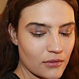 """I'm creating a ray of light on the eye with a metallic strip in a cold nude color right in the middle,"" makeup artist Tom Pecheux explained. To get a rectangular shadow shape on the eye, he used three different shimmer shadows blended together: Estée Lauder Color Instant Intense Eye Shadow Trios in Smoked Chrome, Steel Lilacs, and Sterling Plums. ""Makeup today is very minimal. The inspiration is based on a comfortable, homey, casual indoor place,"" he said."