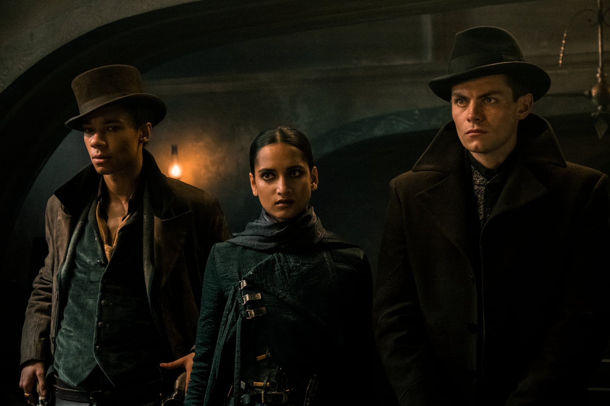 SHADOW AND BONE (L to R) KIT YOUNG as JESPER FAHEY, AMITA SUMAN as INEJ GHAFA and FREDDY CARTER as KAZ BREKKER of SHADOW AND BONE Cr. DAVID APPLEBY/NETFLIX  2021