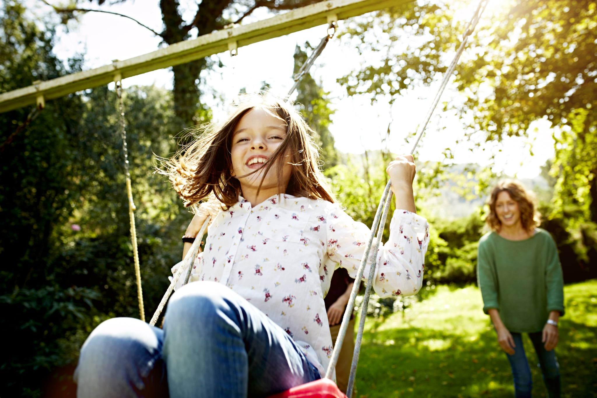 Cheerful mother pushing daughter on swing in sunny park