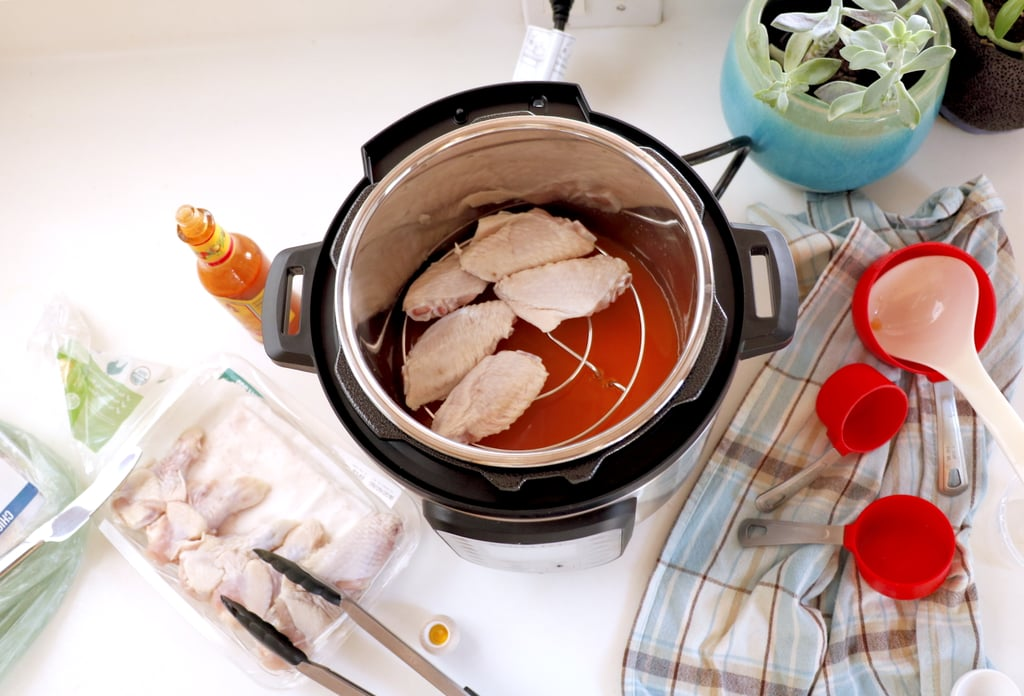 Pour 3/4 cup water and 1/4 cup hot sauce into the bottom of the Instant Pot. Stir. Add the trivet (this comes with most Instant Pots or can be bought online), and place the chicken on top.