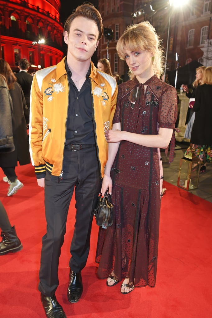 After almost a year of keeping their relationship under wraps, Charlie Heaton and Natalia Dyer certainly seem to have gotten a lot more comfortable showing off their romance. After attending the Burberry x Cara Delevingne Christmas Party over the weekend, the Stranger Things stars arrived in style at the 2017 Fashion Awards in London on Monday. Charlie kept things cool in a yellow bomber jacket, while Natalia stunned in a maroon star-print dress. Charlie and Natalia have been spotted out on multiple dates in London recently, but this is the first time they've hit the red carpet together since going public with their romance in October.