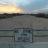 """A """"no diving"""" sign sits over the dried-up Kern River in Bakersfield, CA."""