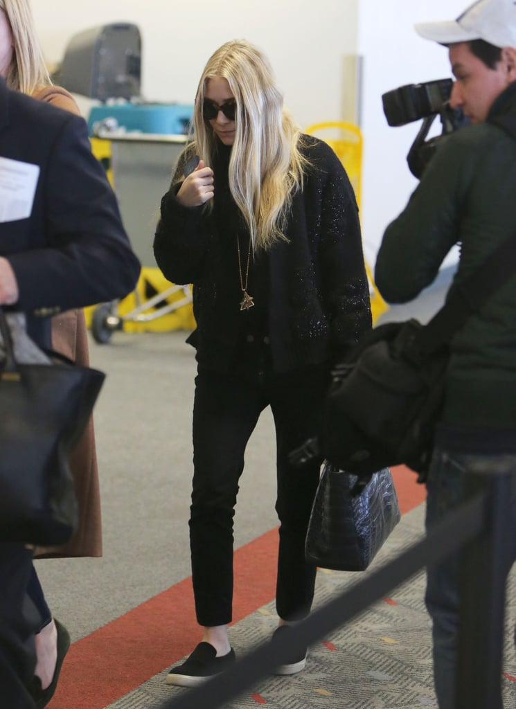 Ashley Olsen took her all-black travel look to sporty heights via Vans slip-on sneakers.