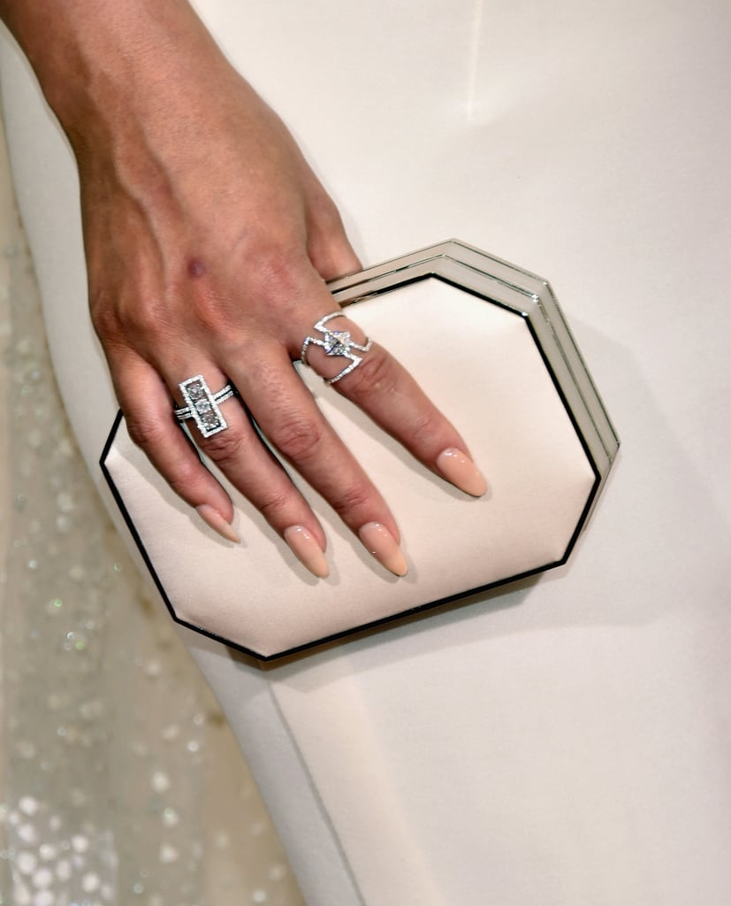 Wearing Lorraine Schwartz rings and carrying a cream box clutch.