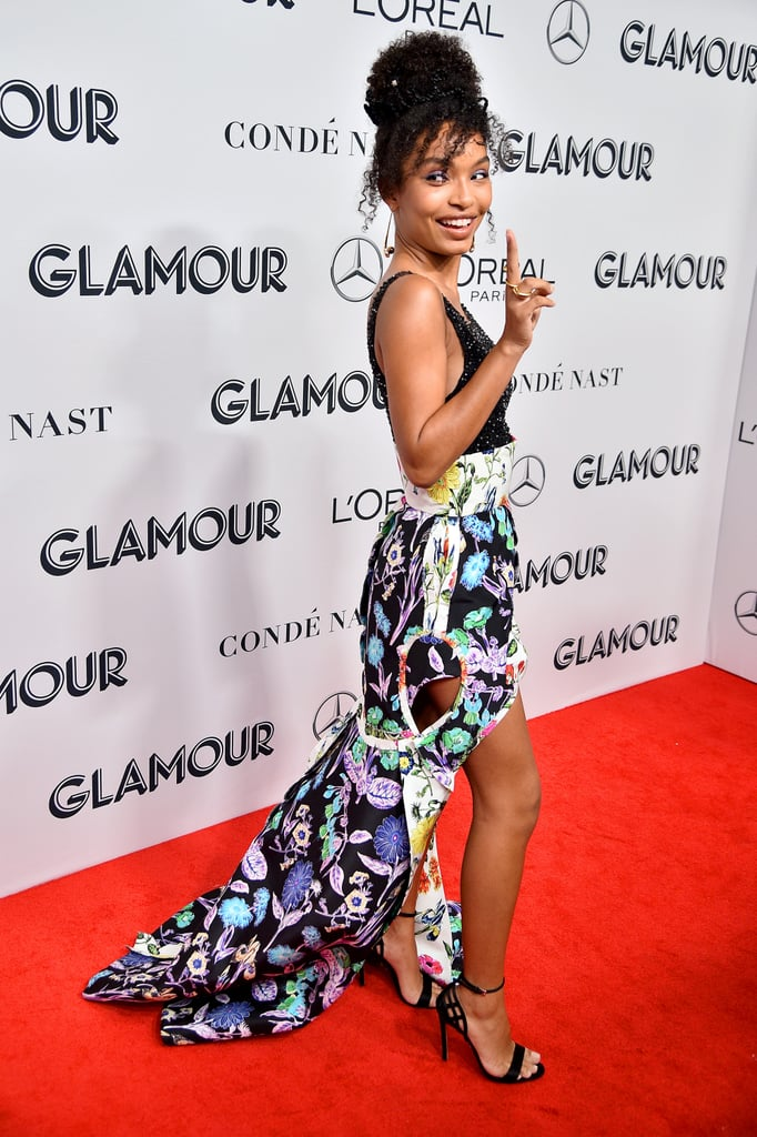 "Yara Shahidi was one of the recipients of the Glamour Women of the Year Awards on Monday night, and she was definitely down for a celebration when she arrived at Alice Tully Hall in NYC for the ceremony. Dressed in a Schiaparelli Couture outfit that combined a sheer, jeweled bodice tucked into an intricate, colorfully printed high-low skirt, Yara once again stole the show with her dramatic look as she accepted her award from Trevor Noah. Yara's look is definitely one you need to see from all angles to appreciate. The fun, short hemline at the front dropped down to a dramatic train at the back, giving it a real ""party in the front, princess in the back"" vibe, but it also featured teardrop-shaped cutouts on the sides, adding even more detail to the already intricate design. By combining contrasting prints on the skirt (some on a dark background, some on white), the dress looked different depending on where your eye fell. Keep reading to see for yourself."