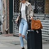 The model had the perfect travel look when she headed out in a jumper coat and distressed jeans, with her suitcase in tow.