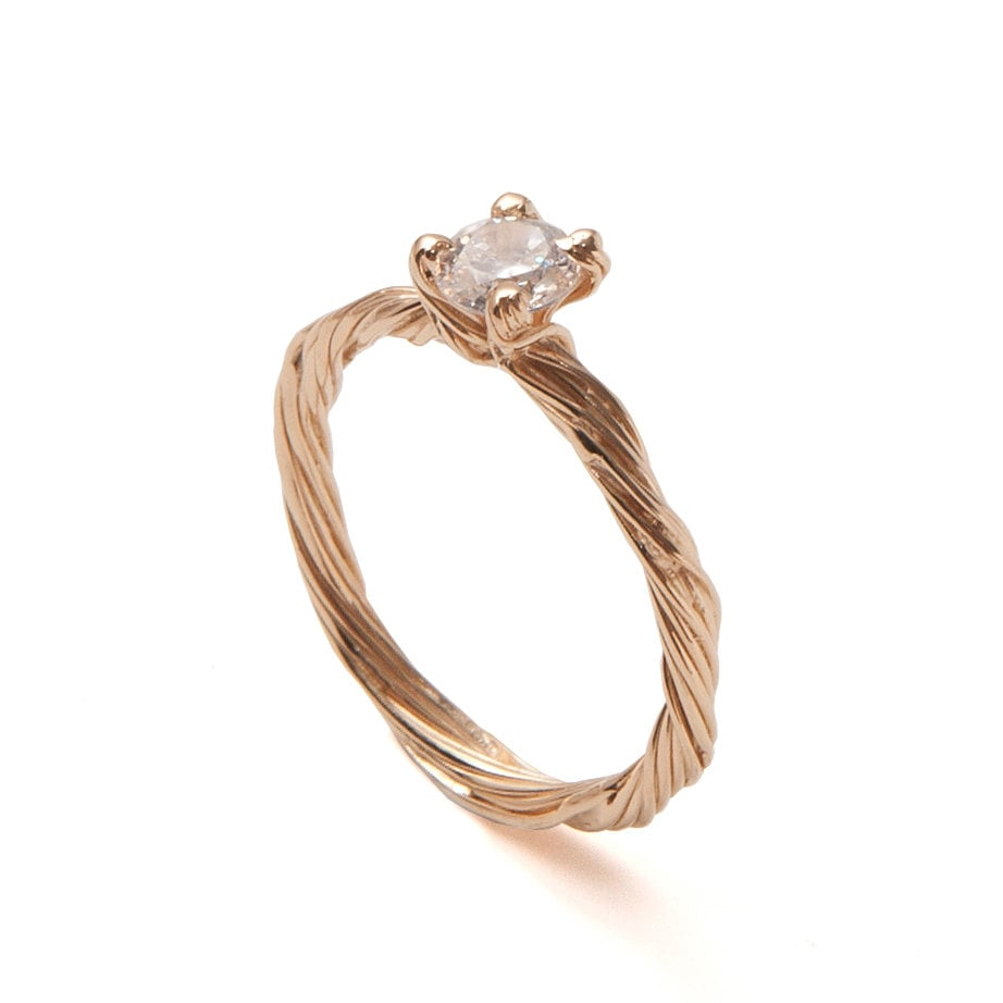 Boho brides will appreciate this handmade 18k yellow gold twig ring ($1,050) set with a clear diamond.