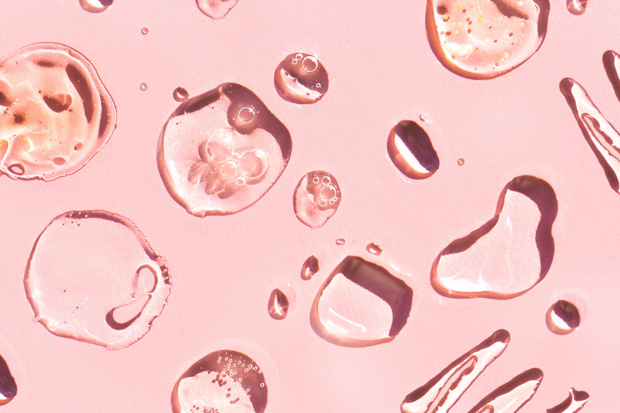 Top view of blots and smears of various lotions and gels spread on pink background. Beauty product of the year