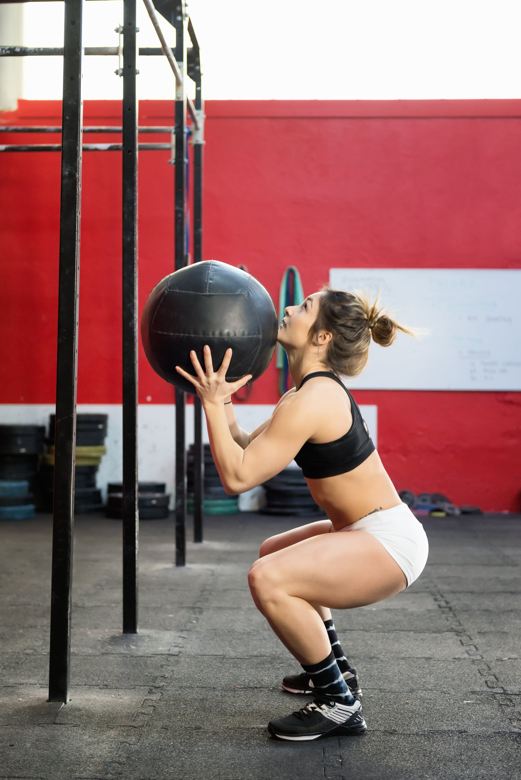 Vertical color profile view image of muscled woman training at gym with a medicine ball.