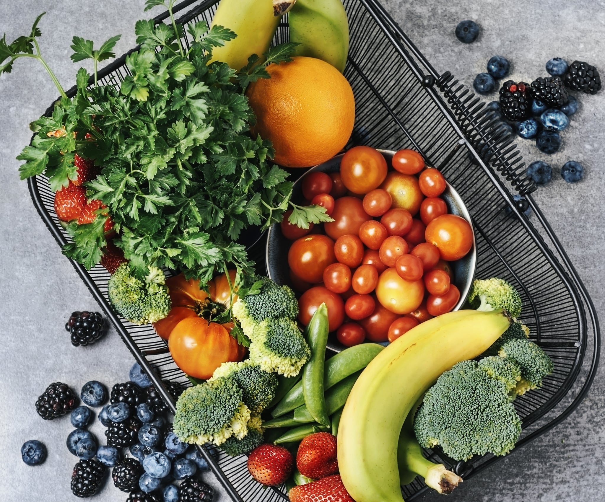 A basket of fresh vegetables, and fruits on grey background