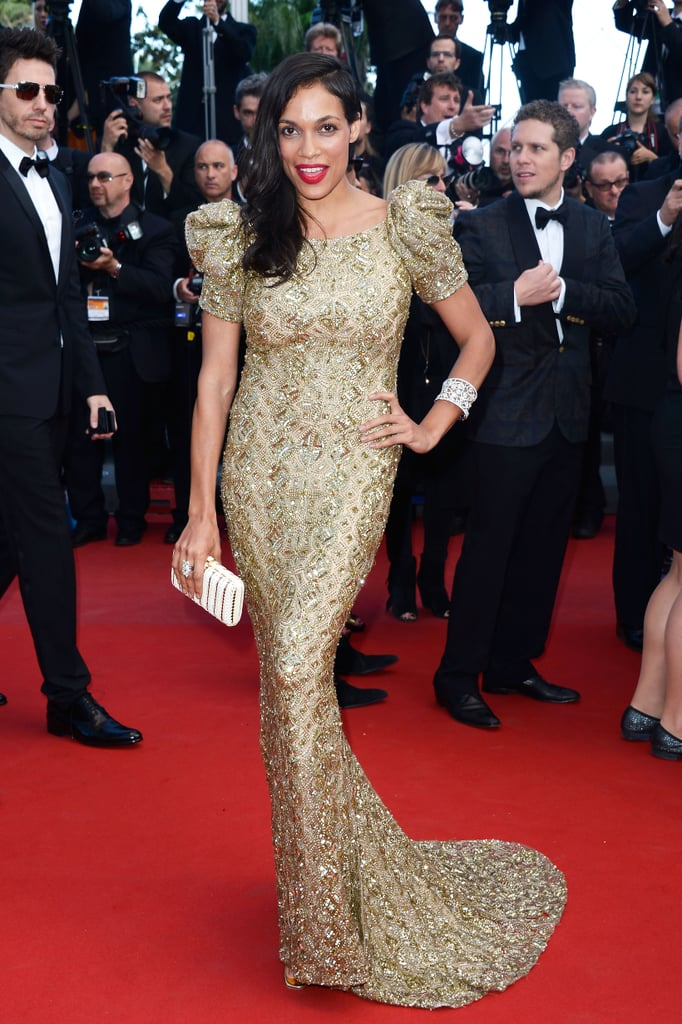 Rosario Dawson lit up the Cleopatra red carpet in a gilded gown and bright red lip.
