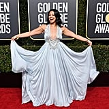 Gina Rodriquez wearing a Reem Acra dress that had a plunging neckline and Chopard jewels.