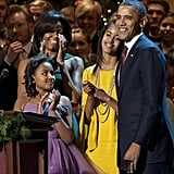 Barack Obama addresses the audience with his family beside him.
