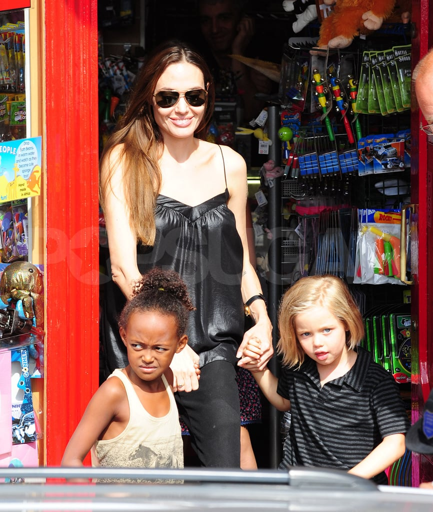 Angelina Jolie held onto the hands of her daughters, Shiloh Jolie-PItt and Zahara Jolie-Pitt, this morning as they left the Toy Station shop in Richmond, London. The store, which sells costumes and playthings for children, is fast becoming one of the Jolie-Pitts' favorites, since Angelina also brought the girls to shop there a couple weeks ago. Angelina and Brad have been showing their kids all that England has to offer during their stay in the country, where Brad's shooting World War Z. After they celebrated Maddox's 10th birthday with a performance of Wicked on Aug. 6, the kids were treated to a puppet show Saturday. Yesterday, Angelina brought Shiloh, Zahara, Maddox, and Pax to see Shrek the Musical.