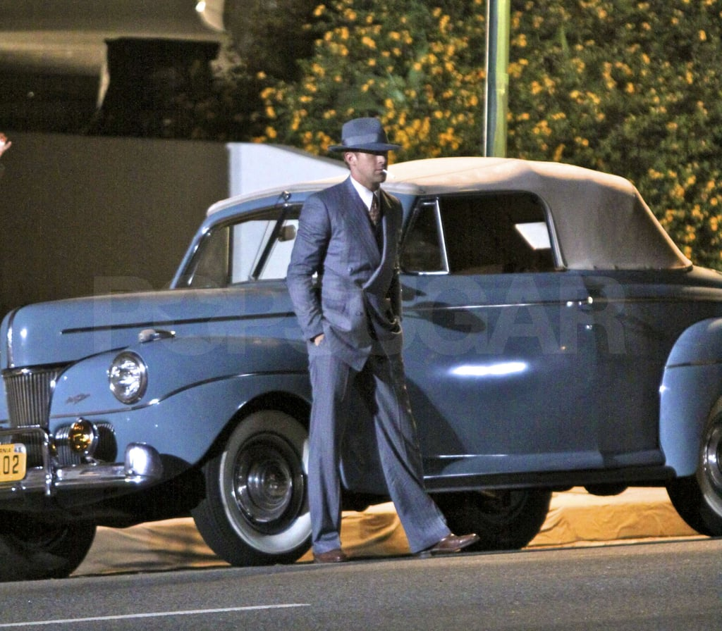 Ryan Gosling leaned against a classic car.