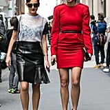 Stylish friends stuck together in a flared leather skirt and a bold minidress, respectively, while walking to the tents.