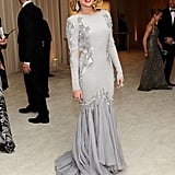 Miley Cyrus channeled Hollywood siren glamour in a grayish silver Roberto Cavalli creation. Her bold red lip and statement earrings injected additional glitz into the look.