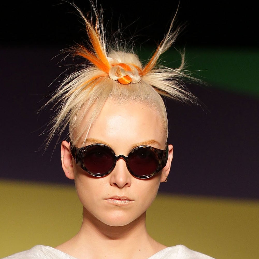 """Hair colour once again made an appearance at Fashion Week at the GInger & Smart show. And once again, Alan White (ghd) was the man behind it. Lifting colours from the collection and adding them to weaves which he worked into models' mohawk styles. It's a """"modern, sophisticated take on the iconic mohawk and '90s rave subculture,"""" he said. The makeup featured that lovely luminosity that we're starting to see lots of but the metallic accents didn't stop at the skin, with gold being added to the brow to give the illusion of a """"revolutionary time traveller,"""" Napoleon Perdis said. OPI's classic Samoan Sand rounded out the whole look. See the hair and makeup teams in action backstage now."""