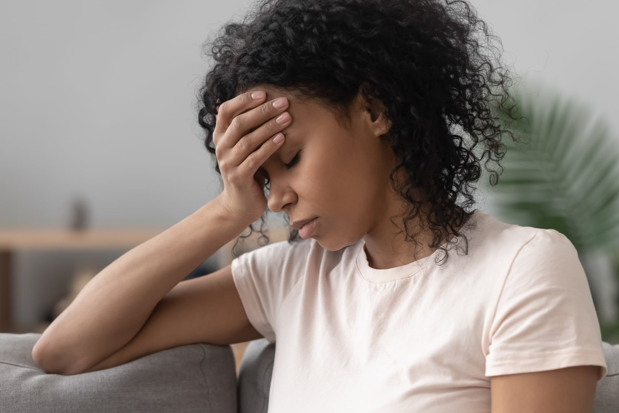 Close up african female sit on couch feels unhappy desperate thinking about personal difficulties mental health problems, 30s sad woman need psychological support goes through divorce break up concept