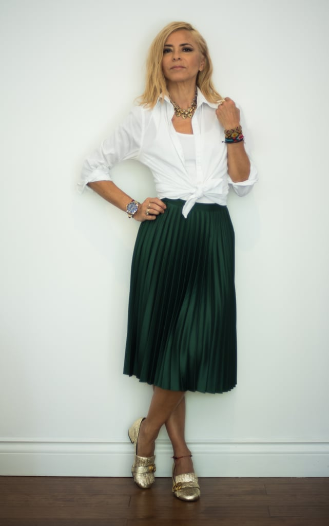 with a pleated green midi skirt a white shirt and gold