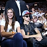 Justin Bieber sat courtside at the Miami Heat game with his bodyguard standing behind him.