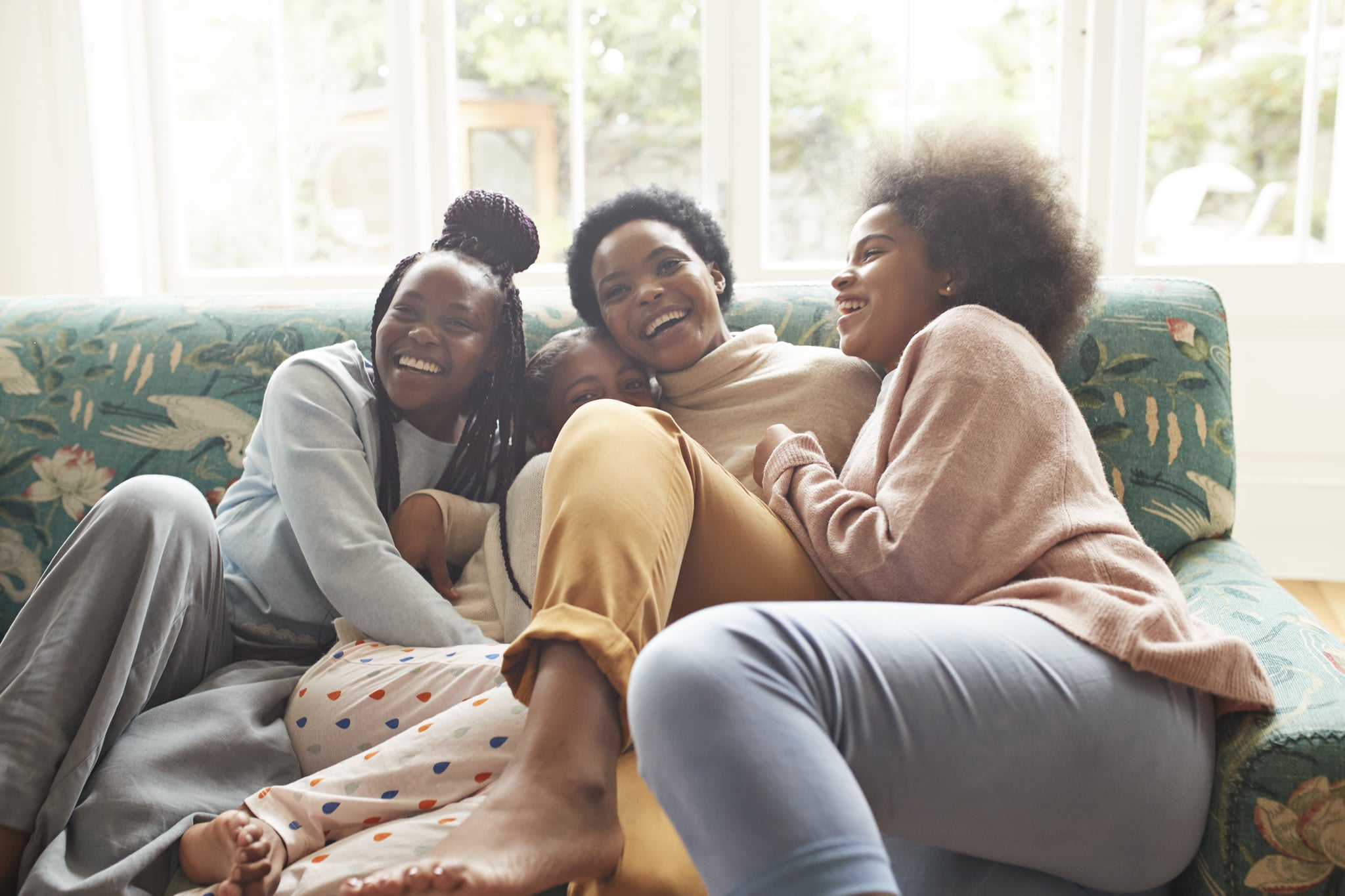 Portrait of happy young woman embracing girls while sitting on sofa at home during Christmas festival