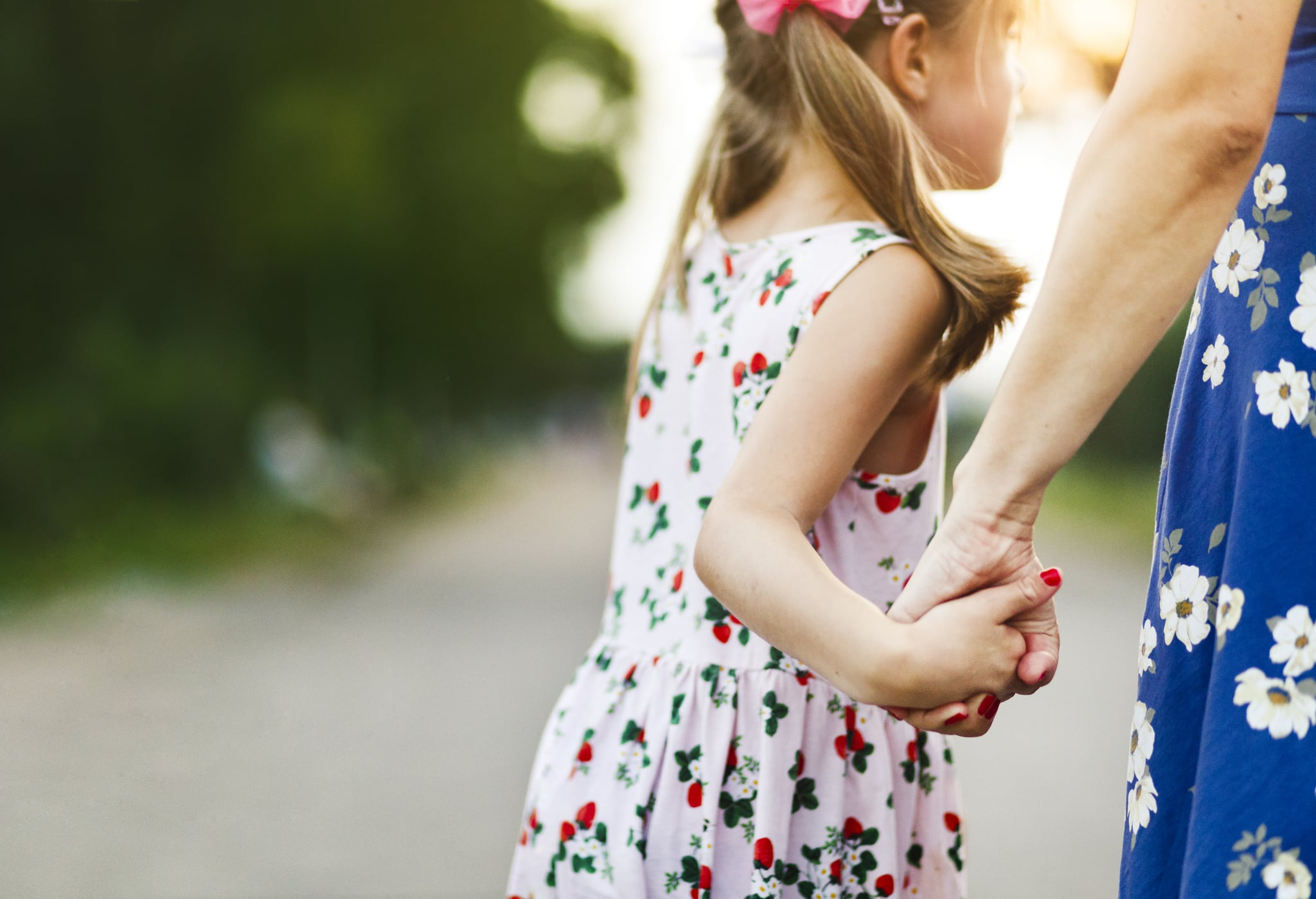Mother and daughter are holding hands outdoors in summer.