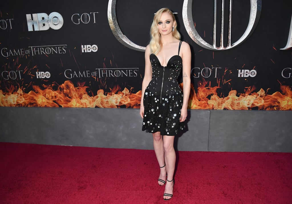 The cast of Game of Thrones celebrated the end of an era on Wednesday night, when they came together for the premiere of the final season of the HBO show. Though they'll no doubt reunite as we head toward the finale, this epic event did mark one of the last times we'll see the whole cast together, so it's no surprise they all pulled out the stops when it came to their outfits.       Related:                                                                                                           Game of Thrones Costars Sophie Turner and Maisie Williams Are the Cutest BFFs               Sophie Turner, who arrived on the arm of her fiancé Joe Jonas, was one such star, picking a Louis Vuitton look first shown less than a month ago during Paris Fashion Week. The Fall/Winter 2019 look comprises a plunging zip-front bustier top with a star print and a black lace skirt with embroidered silver spots, and Sophie teamed it with black sandals with Perspex heels and some seriously stunning diamond earrings. Not only did Sophie's look complement her beau's gray Prince of Wales check suit, it also matched her best friend (and future maid of honor) Maisie Williams's similar black and silver Miu Miu gown. Keep reading to see for yourself, then get a look at some of Sophie's other sexy red carpet moments.
