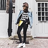 A Black Graphic T-Shirt, Black Pants, a Denim Jacket, and Sneakers