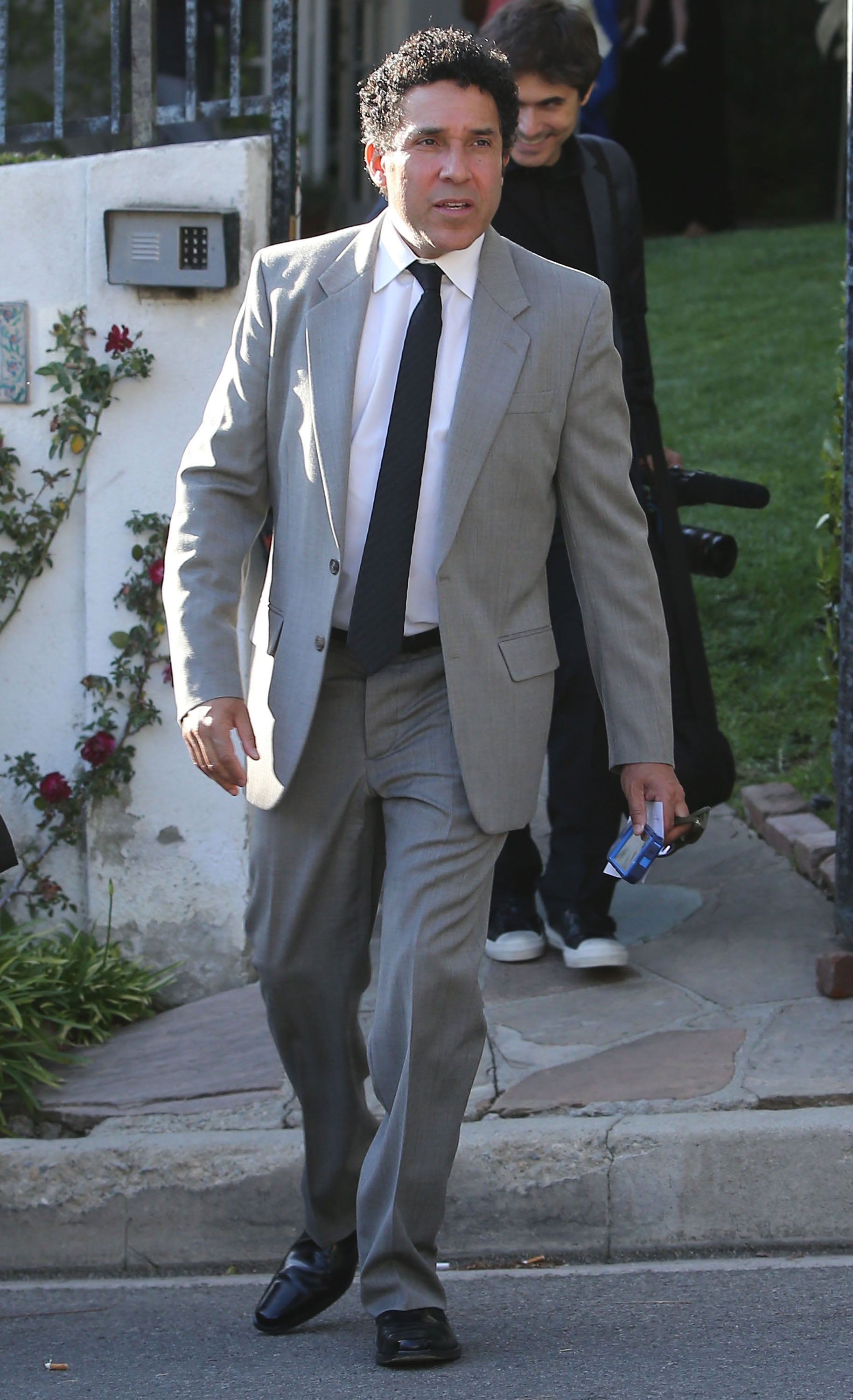 Oscar Nunez wore a gray suit.