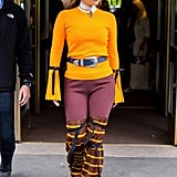 Wearing an orange knit with flared trousers and an Erickson Beamon choker.