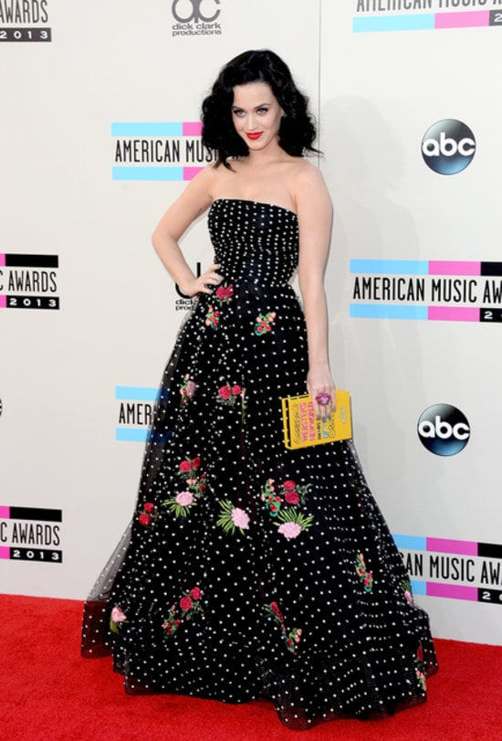 "Katy Perry was one of the first stars to show up to the American Music Awards red carpet, and her look was more ladylike than usual. The singer wore a girlie-yet-grown-up dress – a black polka-dot gown complete with floral appliqués by Oscar de la Renta. She paired the strapless frock with an adorable Olympia Le-Tan ""Webster's New World Handy Pocket Dictionary"" box clutch."