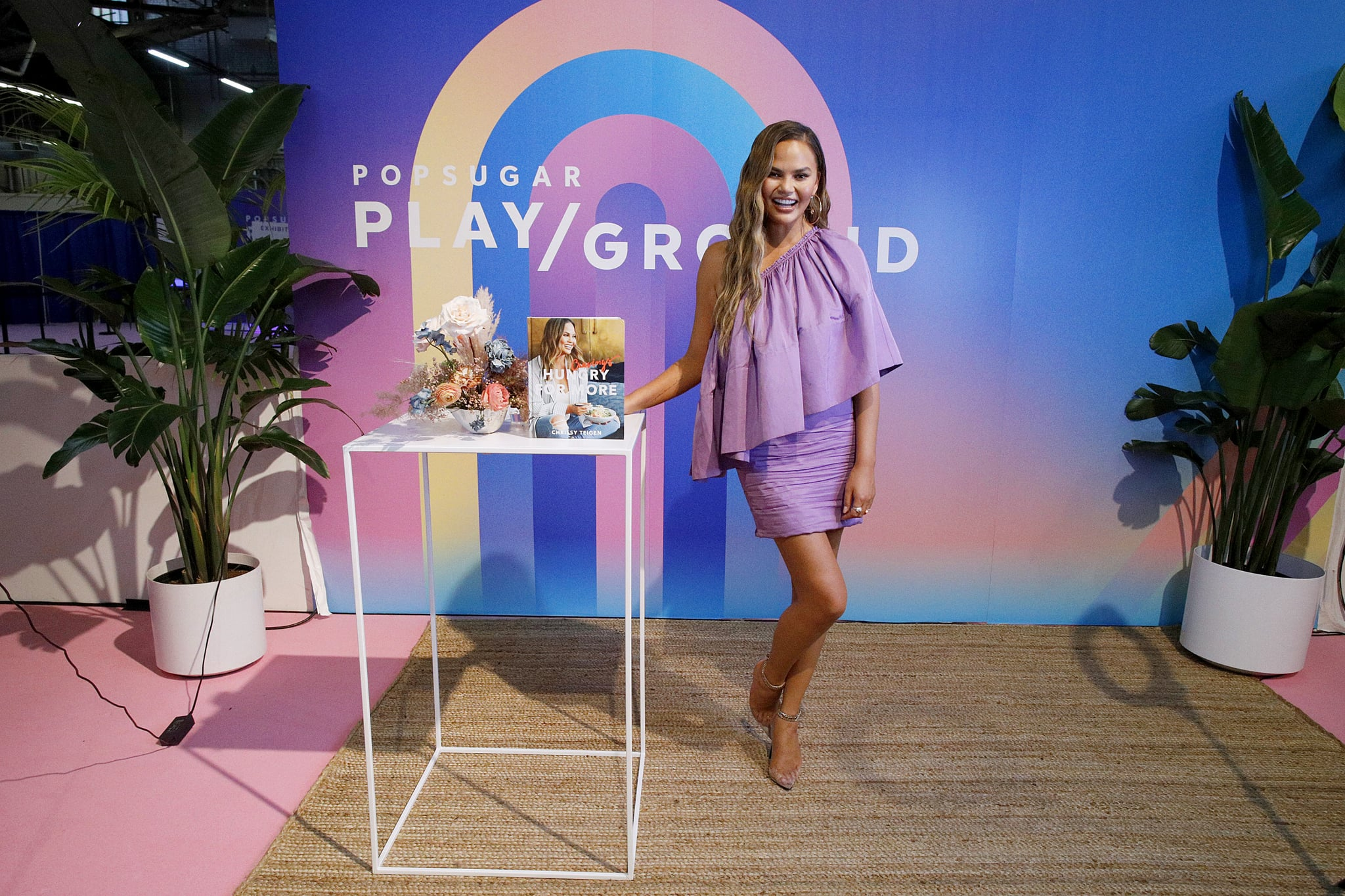 NEW YORK, NEW YORK - JUNE 23: Chrissy Teigen poses with her cookbook during POPSUGAR Play/Ground at Pier 94 on June 23, 2019 in New York City. (Photo by Lars Niki/Getty Images for POPSUGAR and Reed Exhibitions )