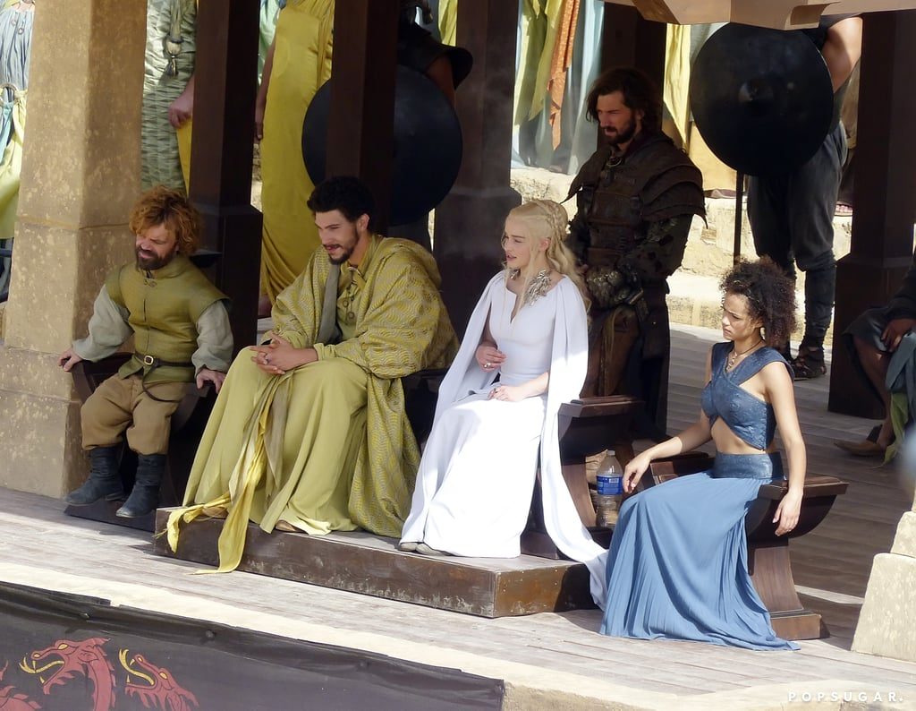 Game of Thrones is currently shooting season five in Spain, which is standing in for Dorne, where the late Oberyn Martell hailed from, and we have a handful of juicy pictures from the set. We can't quite tell which new characters are there yet, but we can see Daenerys (Emilia Clarke) watching over a battle while she wears a white dress we've never seen. If you've read the books, you'll know exactly what's going on here, and the characters who are appearing together is kind of a spoiler as well. Also of note? One of the participants in the duel is the disgraced Jorah Mormont (Iain Glen). What else can you deduce from this sneak peek?