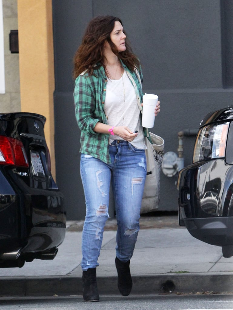 Drew Barrymore wore stylish torn jeans with a plaid shirt.