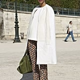 An ultrachic finish on a pair of printed pants with a minimalist white car coat and '70s-inspired platforms.