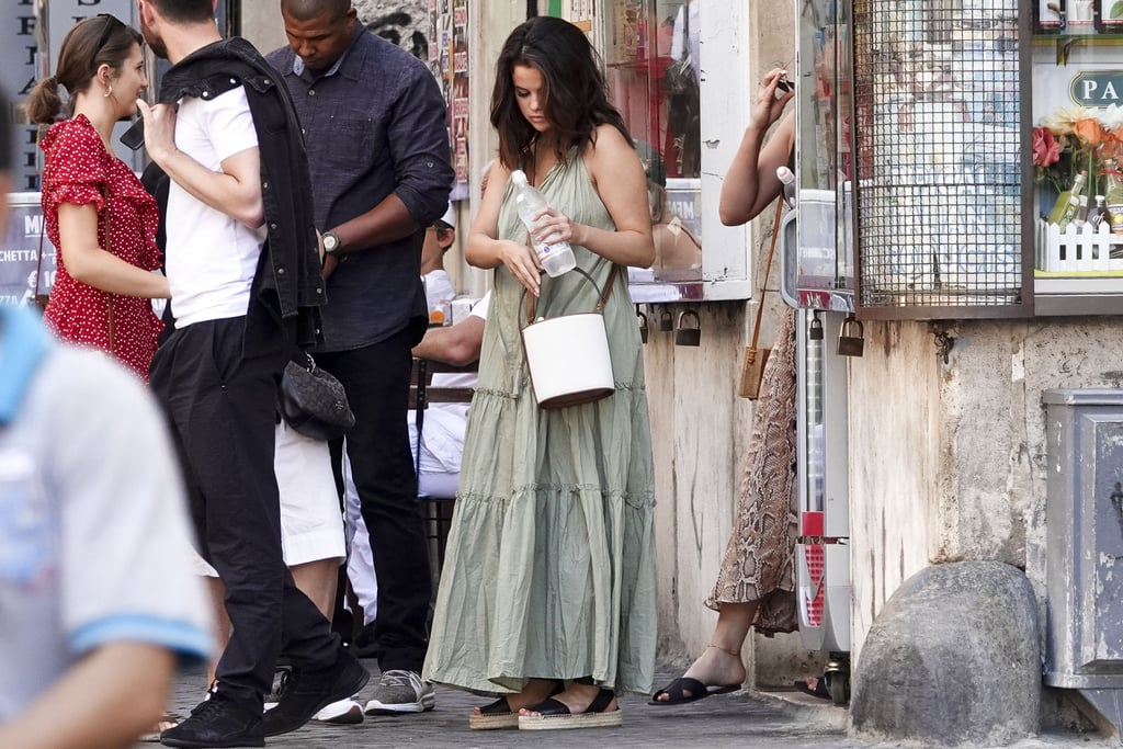 What does Selena Gomez wear on her birthday? One of her many Summer dresses, of course. Days after she celebrated her cousin's wedding, the actress and singer rang in her 27th birthday by strolling around the streets of Rome with friends, dressed in a breezy olive maxi dress and black espadrille sandals. She wore the effortless ruffled dress with a white leather purse and finished with minimal jewelry — when in Rome!  Selena grabbed a birthday lunch with film producer Andrea Iervolino at seafood restaurant Pierluigi, and later posed for photos with fans, beating the heat with an ice-cold water bottle in hand. See more photos of her full outfit ahead, including an up-close look at her darling sandals and chic crossbody bag.       Related:                                                                                                           20 Times We Wanted to Dress Like Selena Gomez