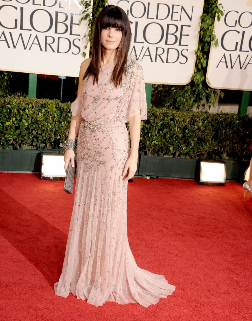 Sandra Bullock stepped out of her limo at the Golden Globes last night wearing an asymmetrical, nude floor-length gown and a dramatic fringe — what do you think of her look? She's back on the West Coast for her presenting duties following a stay in Texas with Ryan Reynolds and a visit to NYC with baby Louis. Weigh in on all of Fab and Bella's love it or leave it polls, and stay tuned for lots more from the show!