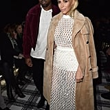 Kim turned out a high-fashion Balenciaga look for PFW, while Kanye turned to his trusty zip-up.