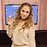Jennifer Lopez posed with a bottle of her latest fragrance, Glowing.