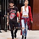 Gigi styled the same tee days before beneath a fuzzy cardigan. She went for a grungy look in ripped boyfriend jeans and Alexander Wang moto boots.