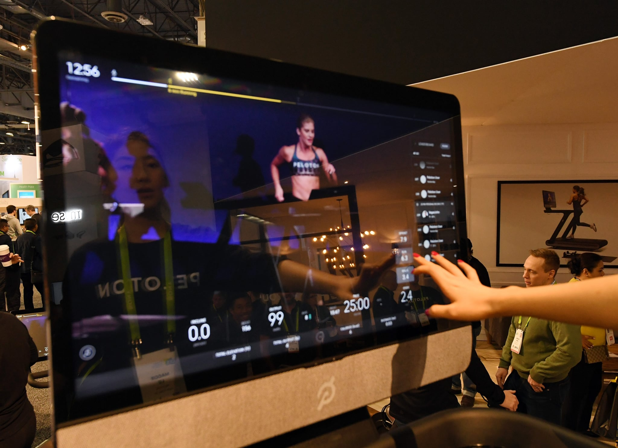 LAS VEGAS, NV - JANUARY 11:  Maggie Lu is reflected in a touch screen as she demonstrates how to select a class on a Peloton Tread treadmill during CES 2018 at the Las Vegas Convention Centre on January 11, 2018 in Las Vegas, Nevada. The USD 3,995 workout machine is expected to be available later this year and features a 32-inch touch screen that connects users to instructors giving live or on-demand fitness classes. CES, the world's largest annual consumer technology trade show, runs through January 12 and features about 3,900 exhibitors showing off their latest products and services to more than 170,000 attendees.  (Photo by Ethan Miller/Getty Images)