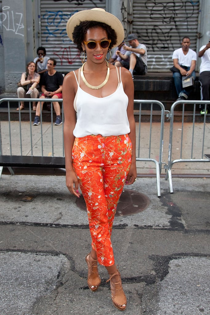 Solange tempered her splatter-paint trousers with a classic white cami, straw hat, and lace-up wedges, then accessorized with a pair of lucite shades and gold jewels.