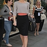 While strutting her svelte stuff in London, Kate sported a chic colorblock Paule Ka look: gray cropped top, black pencil skirt, coral belt, black suede platform Brian Atwood pumps ($754), these gold spiked Melinda Maria earrings ($80), finished with cat-eye shades, and this Alexander McQueen bag ($2,995).