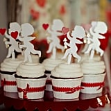 Even though the event was about decorating cookies, it wouldn't have been a Valentine's Day party without some red velvet cupcakes. The desserts were finished off with a Cupid cupcake topper and red ribbon.  Source: Jenny Cookies